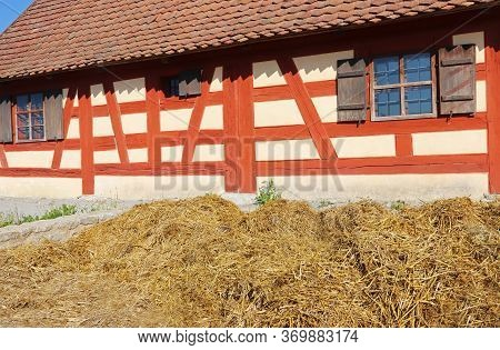 Dung Heap In Front Of An Old Timbered Farmhouse With Red Painted Beams, Shutters And A Dung Heap In
