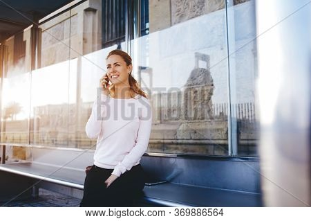 Young Charming Caucasian Female With Trendy Look Use Mobile Phone While Waiting Taxi On Bus Stop,