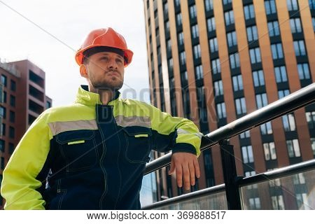 A Clean Builder Shows Sincere Emotions Of Indignation. Man In Special Clothes And Helmet Shows Hosti
