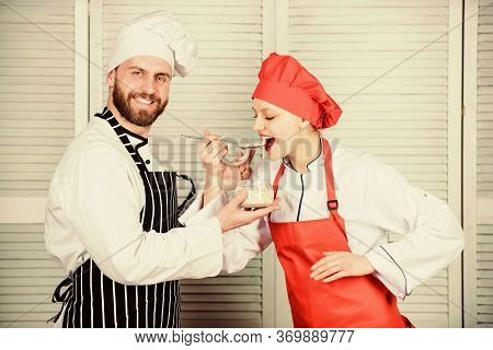 Woman And Bearded Man Cooking Together. Couple Compete In Culinary. Try Ingredients Before Cook. Est