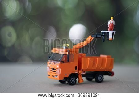 Miniature Electrician On Picker Car Crane. Concept Of Electrician Worker Repair Or Reinstall Traffic