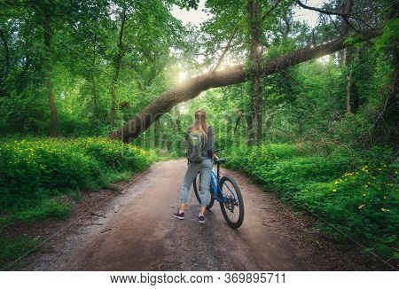 Woman Riding A Bicycle In Forest In Spring At Sunset. Colorful Landscape With Sporty Girl With Backp