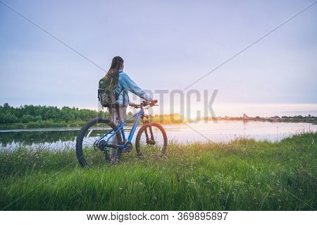 Woman With Bicycle On The Hill Near The River At Sunset In Spring. Landscape With Sporty Girl With B