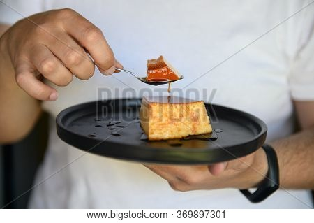 Brazilian Sweet - Condensed Milk Pudding. A Man Holding A Plate And Took A Piece Of Pudding With A S