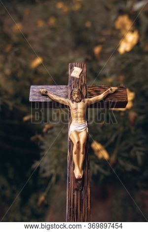 Beautiful Old Wooden Crucifix With Dust And Spiderweb In A Backdrop Of Garden With Cosmos Flowers.