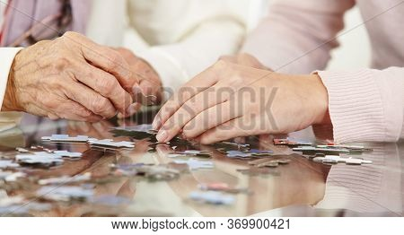Hands of senior woman and young woman with puzzle on the table