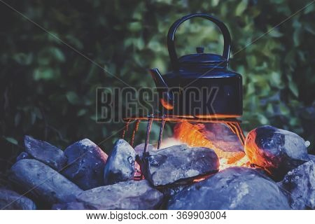 Adventure Cooking During Camping: Metal Kettle Boiling On A Campfire, Surrounded By Stones. Back To