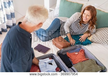 High angle view of mature man packing stuff. Happy mature couple packing clothes into suitcase. Top view of cheerful smiling wife lying on bed with husband arranging accessories in bag for travel.