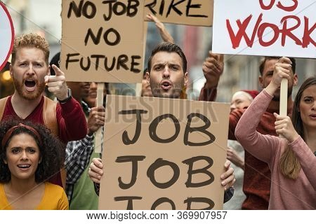 Group of demonstrators with banners protest for job and equal salaries. Protestors people holding signs and posters strike for unemployment. Group of multiethnic men and women protesting with placards