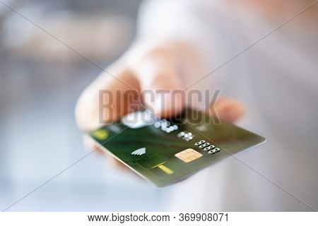 Close up of woman hand showing credit card. Detail of girl giving credit card for electronic payment. Female hand pass debit card to cashier for payment.