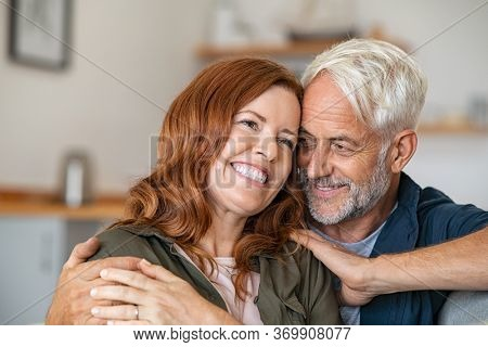 Cheerful mature couple embracing while sitting on couch. Senior man giving woman a hug while looking at her with love. Loving old husband embracing from behind smiling wife at home.