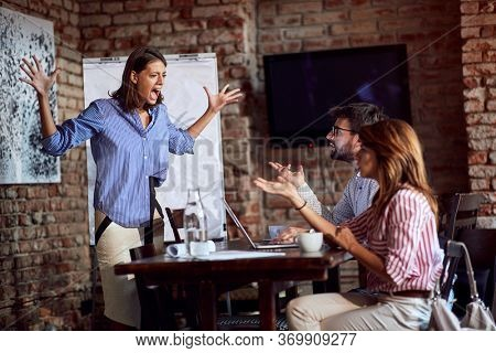 furious woman yelling with arms spread on a husband in cafe with another young female. rage, adultery, jealousy concept