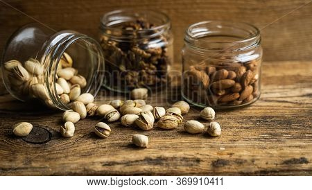 Pistachios Scattered On The Vintage Table From A Jar And With Other Nuts On Background. Pistachio Is