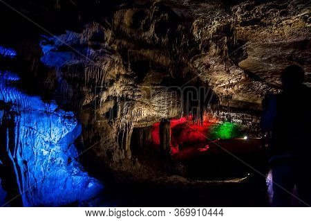 A Deep, Wet Cave With Illuminated Walls And Stalactites