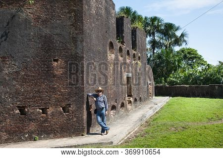 Old Fortress Brick Wall Of Fort Zeelandia On A Clear Sunny Day And A Standing Man In A Cowboy Hat, G