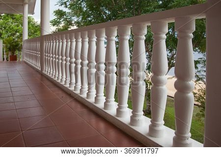View Of The Balustrade Of The Verandah Made Of White Turned Wooden Spindles On A Sunny Day Against T