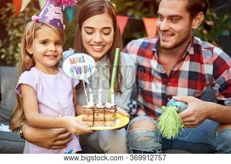 B-day girl with parents holding b-day cake and making a wish