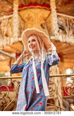 From Below Cheerful Blond Woman In Straw Hat With Brim And Flowered Blue Dress Smiling Away, While L