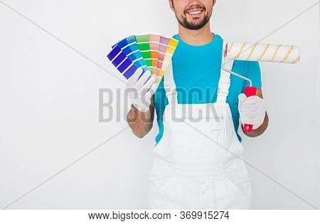 Crop Smiling Professional Male Decorator In Overall And Gloves Holding Colorful Palette Samples And