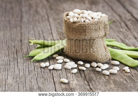 Uncooked Dried White Haricot Beans In Burlap Sack With Fresh Raw Green Beans Pod Plant On Rustic Tab
