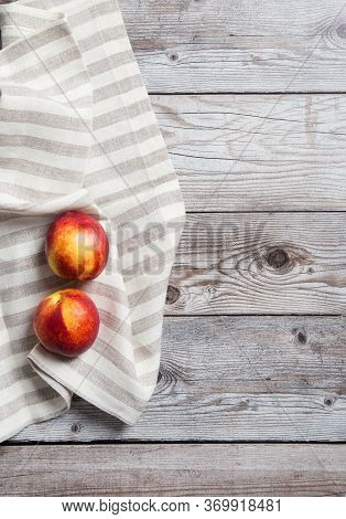 Nectarines On Wooden Background With Striped Napkin. Copy Space, Flat Lay, Top View