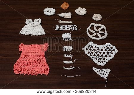 Crochet Dresses And Table Tops, View Of Yarn Ball And Needle Along With Crochet Patterns