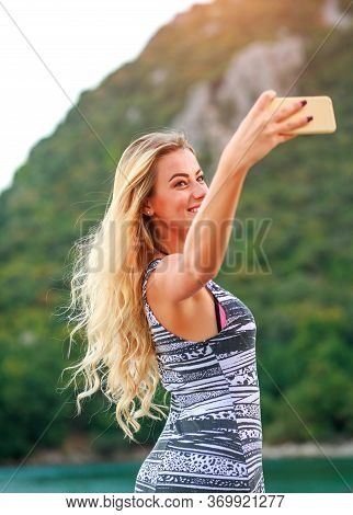 Charming Girl Takes Selfie With A Smartphone By The Sea On A Background Of Green Mountains, Cirali B