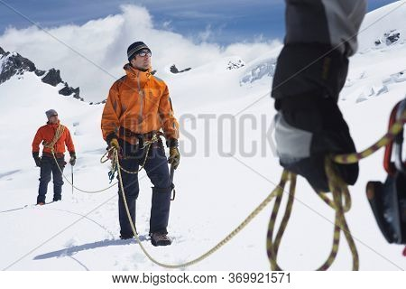 Three hikers joined by safety line in snowy mountains mid section on front man