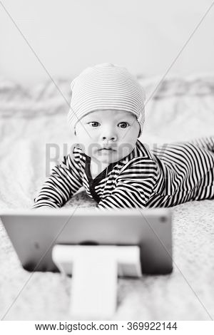 Baby With Tablet Pc On The Bed