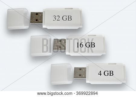 White Usb Memory Sticks, 4 Gb, 16 Gb And 32 Gb On White Background, With Their Lids Off