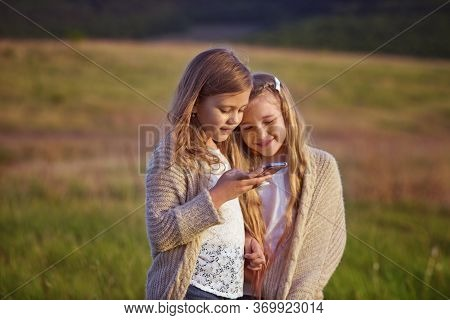 Two Funny Happy Girls With Phone Outdoors