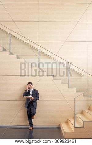 Portrait of attractive businessman using smartphone while leaning on wall in office