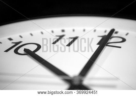 Closeup On The Pointers Of A Clock Marking A Few Seconds Before Ten O'clock - Black And White Render
