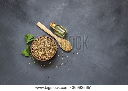 Glass Bottle Of Coriander Essential Oil With Coriander Powder And Fresh Cilantro Leaves On Rustic Ta
