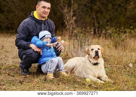 Father With Little Son And Dog Outdoors