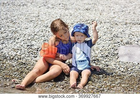 Little Brother And Sister Playing On The Beach Near The Sea