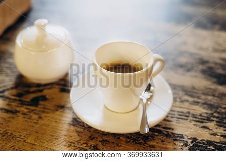 Aromatic Fresh Coffee In A White Cup. Americano With Sugar Bowl On Table In Cafe. Americano In A Sma