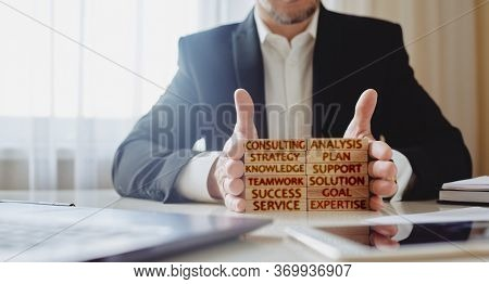 Consulting Concept. Man Stacks Wooden Blocks With Inscriptions Analysis, Strategy, Plan, Knowledge,