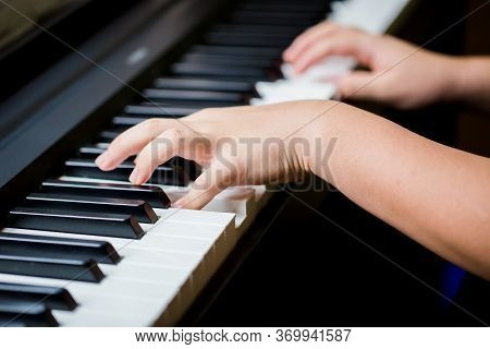 Selective Focus To Kid Fingers And  Piano Key To Play The Piano. There Are Musical Instrument For Co