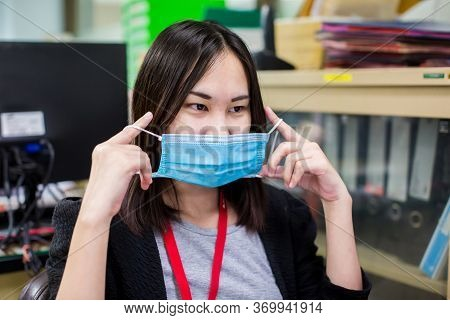 Asian Woman Employee Is Wearing Medical Facial Mask Working Alone As Of Social Distancing Policy In