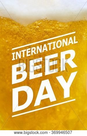 Close-up View Of Beer Glass With Text Overlay On It - International Beer Day. Glass Of Cold Light Be