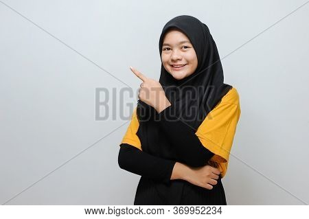 Cute Young Beautiful Muslim Woman Pointing At Copy Space. Cheerful Muslim Woman Pointing At Copy Spa