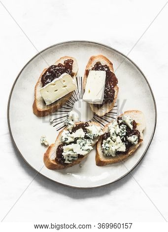 Crostini With Fig Jam, Gorgonzola And Brie Cheese  On A Light Background, Top View