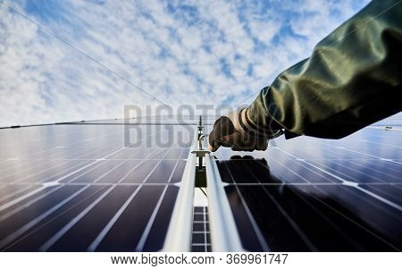 Close Up Of Male Worker Hand In Glove Installing Photovoltaic Solar Panel With Beautiful Cloudy Sky