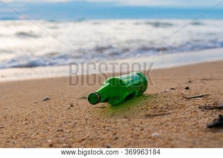 A Bottle Of Beer Lies On The Seashore, Garbage On The Beach, Dirty Tropical Sand, Garbage In Thailan