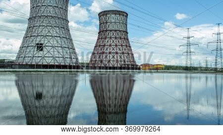 View Of The Power Plant And Cooling Towers. The Smoke Goes Out From A Cooling Tower Of An Operating
