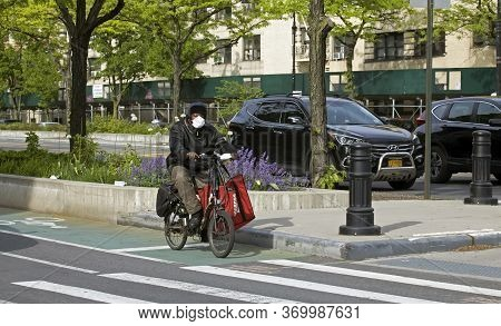 Bronx, New York/usa - May 18, 2020: Man Wears Mask As He Rides Bike To Do Food Delivery During Coron