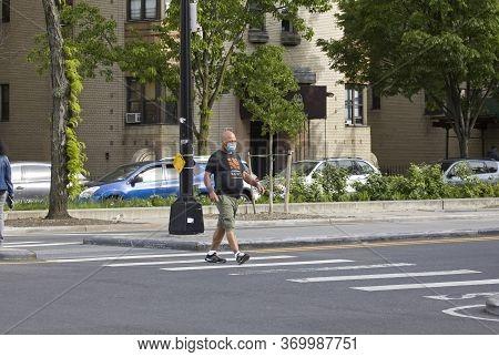 Bronx, New York/usa - May 18, 2020: Man Crossing Street Wearing Mask During Covid-19 Pandemic.