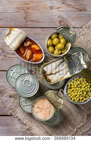 Assortment Of Different Canned Preserved Vegetables, Meat, Fish, Seafood In Tin Cans On A Wooden Tab