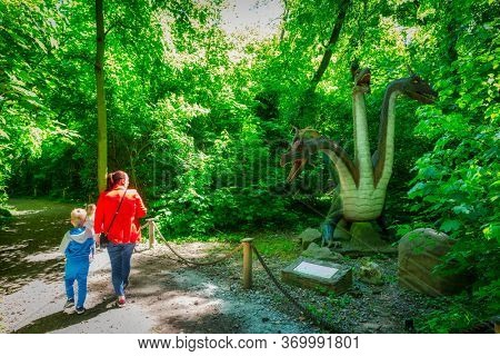 Malbork, Poland - June 1, 2020: Family walking at realistic dragon at the Dino Park in Malbork, Poland. Dino Park is a tourist attraction with moving dinosaurs and dragons.